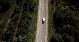 Flyg- sikt som flyger över den gamla lappade skogvägen för två gränd med bil skåpbil flyttning gräsplanträd av täta trän som växe stock video