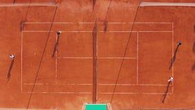 flyg- sikt Spelare spelar tennis på den orange domstolen stock video