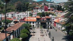 Flyg- sikt - surret flyger över en liten färgrik spansk stad som lokaliseras i bergen Färgrika hus av forntida stock video