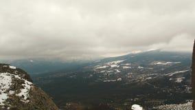 Flyg- sikt uppifrån på gamla berg och skogen som täckas av snö mot gråa moln skjutit solnedgång för sky för aftonliggandehav lager videofilmer
