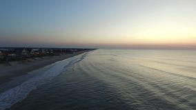 Flyg- sikt/video rörande öst på soluppgång längs stranden av den norr Topsail ön arkivfilmer