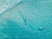 Flyg- skott av simmare på en härlig strand med blått vatten och vit sand - djupt vatten arkivfoto