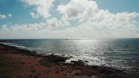 Flyg- skott av solljusreflexionen på det krabba havet under solnedgång Vågor som slår mot den steniga stranden Havhavskust arkivfilmer