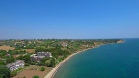Flyg- skott av stranden från över med blått vatten, Nea Mihaniona Thessaloniki Greece, uppåtriktad rörelse med surret lager videofilmer