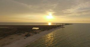Flyg- skott för frysningram av en fyr och ett torn på den Dzharylhach ön på solnedgången stock video