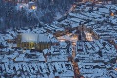 Flyg- skymningsikt av den snöig rådfyrkanten, Brasov, Rumänien Royaltyfria Bilder