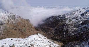 Flyg- flyg som är rörande framåtriktat över den snöig bergkantdalen med moln och solestablisher Alpint löst för utomhus- snö lager videofilmer