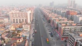 Flyg som oFlying diagonalt surret över en upptagen huvudväg Passera till och med de tätt framkallade Chinesever husen i den kines arkivfilmer