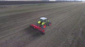 Flyg- spårningvideo: traktoren bearbetar jorden på fältet, fortskrider diagonalen av ramen stock video