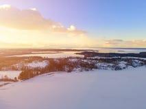 Flyg- surrsikt av ett vinterlandskap Skog och sjöar för snö dold uppifrån Soluppgång i natur från en sikt för fågelöga aer fotografering för bildbyråer