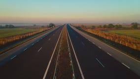 Flyg- surrsikt av solnedgången över en huvudväg och jordbrukfält stock video