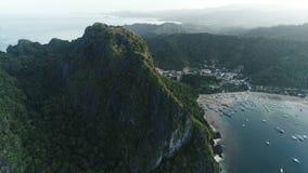 Flyg- surrskott av det höga berget som täckas med den tropiska skogen och fartyg som ankras i fjärden tropisk liggande arkivfilmer