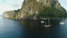 Flyg- surrskott av det höga berget som täckas med den tropiska skogen och fartyg som ankras i fjärden tropisk liggande stock video