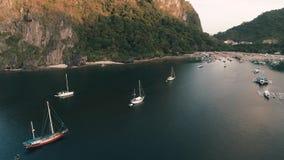 Flyg- surrskott av det höga berget som täckas med den tropiska skogen och fartyg som ankras i fjärden tropisk liggande lager videofilmer