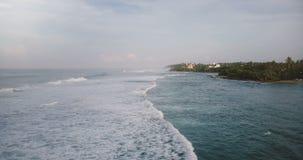 Flyg- surrskott av fantastiska skumma havvågor som når och bryter på den tropiska semesterortkusten med hotell och hus lager videofilmer