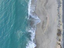 Flyg- surrskott av vågor och sand arkivfoto