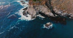 Flyg- surrskott för bästa sikt av härliga blåa havvågor som kraschar över solig stenig kustlinje i Big Sur Kalifornien lager videofilmer