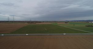 Flyg- väg för innehåll för fågelsiktssurr med ljus trafik på utvändiga stad och åkermarker stock video