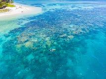Flyg- ?verkant ner folk som snorklar p? det tropiska karibiska havet f?r korallrev, turkosbl?tt vatten Indonesien Banyak ?ar Suma royaltyfria foton