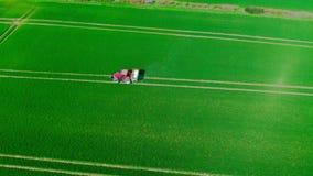 Flyg- video av fördelande gödningsmedel för röd traktor på ett fält arkivfilmer
