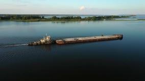 Flyg- videopn flodlangarefartyg som transporterar pråm med torr last i mitt av sommarfloden, Centraleuropa lager videofilmer
