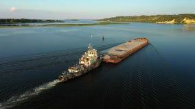 Flyg- videopn flodlangarefartyg som transporterar pråm med torr last i mitt av sommarfloden, Centraleuropa arkivfilmer