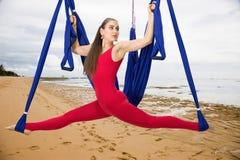 Flyg- yoga eller Anti--gravitation yoga För flugayoga för ung kvinna övande asana utomhus arkivfoto