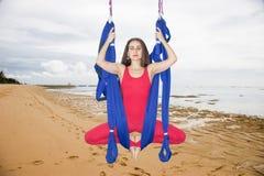 Flyg- yoga eller Anti--gravitation yoga För flugayoga för ung kvinna övande asana utomhus royaltyfri foto