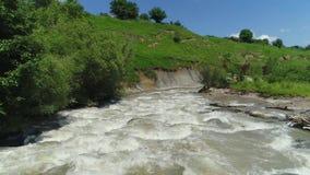Flyga över en bergflod, en stark ström av vatten Från luften stock video