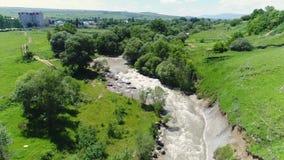 Flyga över en bergflod, en stark ström av vatten Från luften arkivfilmer