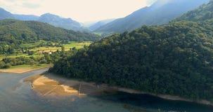 Flyga över en sjö med sikten av en skog och berg arkivfilmer