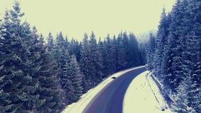 Flyga över en vinterskogväg i bergen lager videofilmer