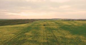 _ Flyga över fältet med en Canola Åkerbruk traktor som besprutar fältet för sommarskördCanola arkivfilmer