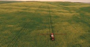 Flyga över fältet med en Canola Åkerbruk traktor som besprutar fältet för sommarskördCanola lager videofilmer