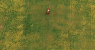 Flyga över fältet med en Canola Åkerbruk traktor som besprutar fältet för sommarskördvete Flyg- video arkivfilmer