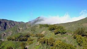 Flyga över frodigt landskap och vulkaniska berg arkivfilmer