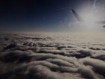 Flyga över molnen och de skinande vingarna arkivfoton