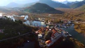 Flyga över sjön och den gamla staden Virpazar, Skadar sjö i Montenegro lager videofilmer