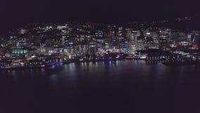 Flyga in i stad på natten, över reflekterande vatten 4k för hamn lager videofilmer