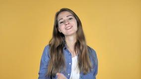 Flyga kyssen, genom att vända runt om den nätta kvinnan som isoleras på gul bakgrund stock video