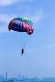 Flyga med en hoppa fallskärm över havet Arkivbild
