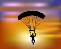 Flyga med hoppa fallskärm i solnedgången Arkivfoto