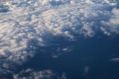 Flyga ovanför molnen i middagar arkivfoto