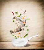 Flyga rå hela forellfiskar med grönsaker, olja och kryddaingredienser ovanför stekpannan för smaklig matlagning på skrivbordköksb royaltyfri bild