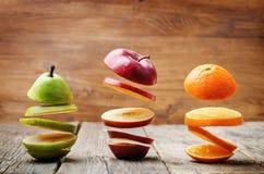 Flyga skivor av frukt: äpple päron, apelsin arkivbild