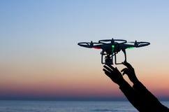 Flyga surret med kameran på himlen på solnedgången Arkivfoto