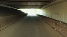 Flyga till och med en kort tunnel under bron stock video