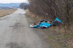 Flyga tippat rackar ner på dumpat i en parkeringsplats invid väg i en landsgränd Överhopa av det olagligt dumpade hushållet racka royaltyfri bild