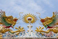 Flyga tvilling- guld- drakar med bollen Royaltyfria Bilder