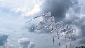 Flyga vita flaggor på flaggstång mot bakgrunden av den ljusa molniga himlen under en utomhus- händelse stock video